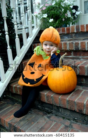 Cute little girl, wearing a pumpkin costume, leans impatiently on a pumpkin.  She is waiting for Halloween to arrive. - stock photo