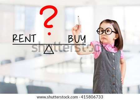 Cute little girl wearing business dress and writing rent and buy compare on balance bar. Office background. - stock photo