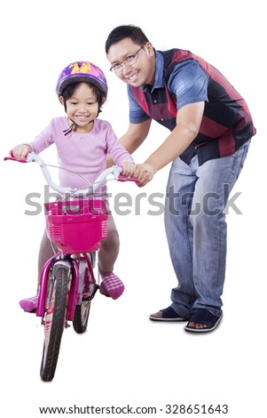 Cute little girl wearing helmet and try to ride a bicycle with her dad, isolated on white background - stock photo