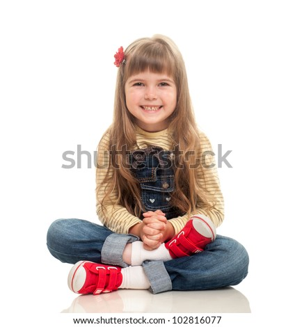 cute little girl wearing jeans overall sitting on the floor and smiling on white background - stock photo
