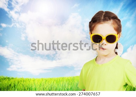 Cute little girl wearing sunglasses against bright nature background - stock photo