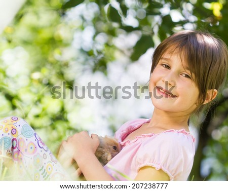 Cute little girl with a bunny rabbit - stock photo