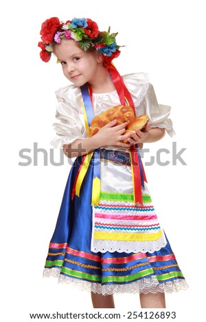 Cute little girl with a nice smile in the national costume of Ukraine holds the pies on Food and Drink - stock photo