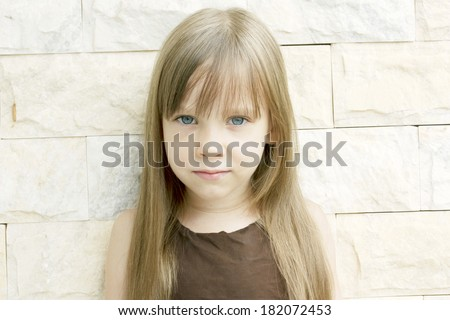 Cute little girl with a serious angry expression, outside, wall background - stock photo