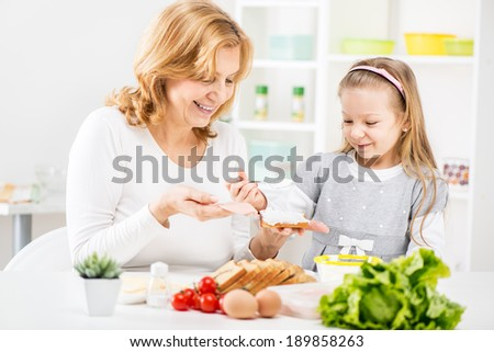 Cute little girl with Beautiful grandmother making a Sandwich in the kitchen. - stock photo