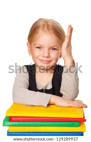 Cute little girl with books raising a hand to answer. School portrait. Little pupil. Isolated on white background - stock photo
