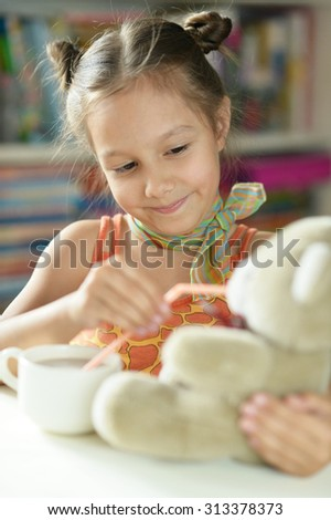 Cute little girl with cup and teddy bear  on the table - stock photo