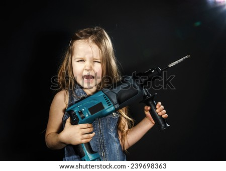 Cute little girl with drilling machine in her hands ready to professional constructing work - stock photo