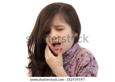 Cute little girl with her hand held to her face with painful expression showing toothache - stock photo