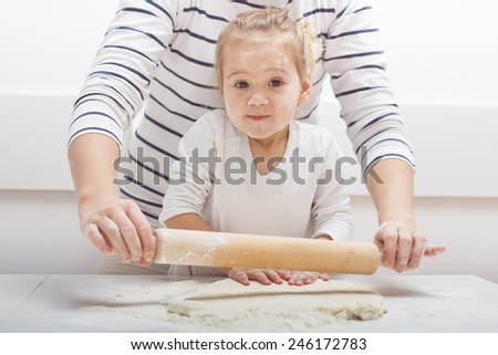 Cute little girl with her mother kneading dough at home. - stock photo
