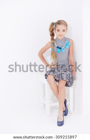 Cute little girl with long blond hair posing on the chair in studio. - stock photo
