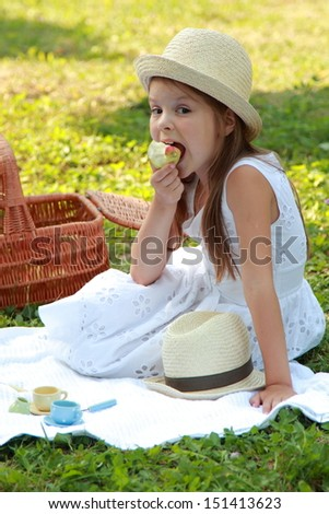 Cute little girl with long healthy hair in a white dress eats a pear in a sunny summer day on a picnic - stock photo