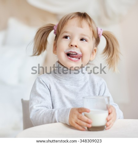 Cute little girl with milk mustache holding glass of milk - stock photo
