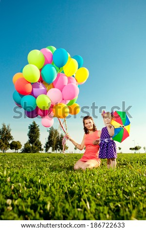 Cute little girl with mother colored balloons and rainbow umbrella holding  in the  park. Smiling child and mom on a field with flowers. Kid with mum rest on the nature.  Family outdoor - stock photo