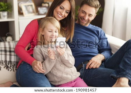 Cute little girl with parents playing by mobile phone at home  - stock photo