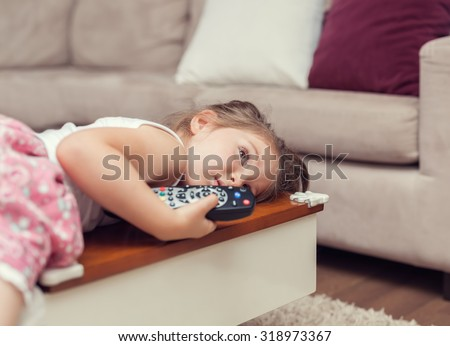 cute little girl with remote control lying on coffee table and watching tv - stock photo