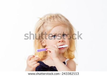 Cute little girl with toothbrush in her hand on white background - stock photo