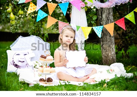 Cute little girl with with empty board with space for text on party background - stock photo