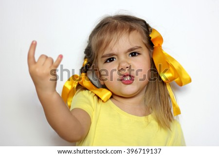Cute little girl with yellow bows and yellow T-shirt shows horns (love hard rock) gesture over white background, sign and gesture concept - stock photo