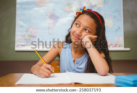 Cute little girl writing book in classroom - stock photo