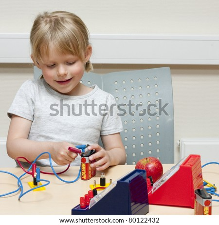 Cute little girl (5 years old) doing experiments with electricity - stock photo