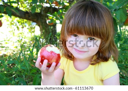 Cute little girls eating red delicious apple - stock photo