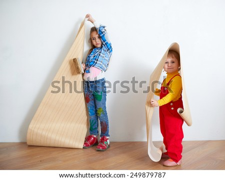 Cute little girls hanging wallpaper. Decorating the wall - stock photo