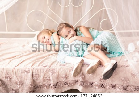 Cute little girls in fashion dresses with spring flowers - stock photo