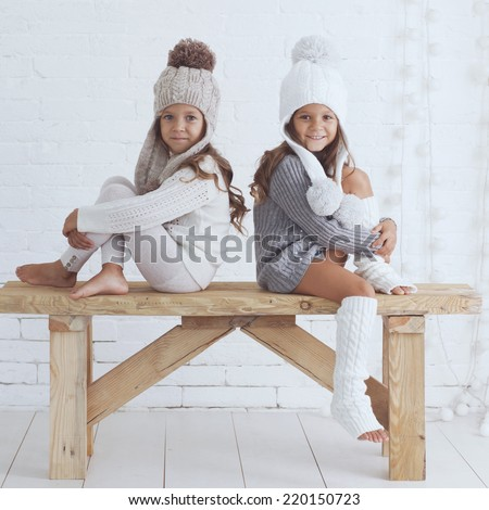 Cute little girls of 5 years old wearing knitted trendy winter clothes posing over white brick wall - stock photo
