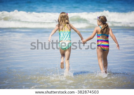 Cute little girls playing at the beach together during summer vacation  - stock photo