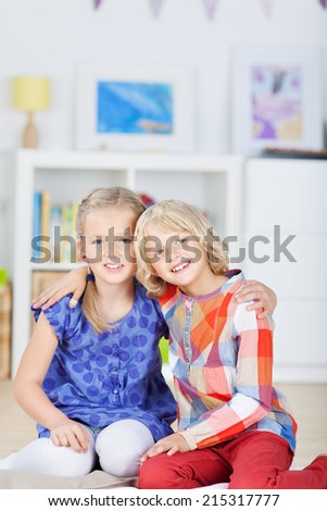 Cute little girls with arms around sitting together at home - stock photo
