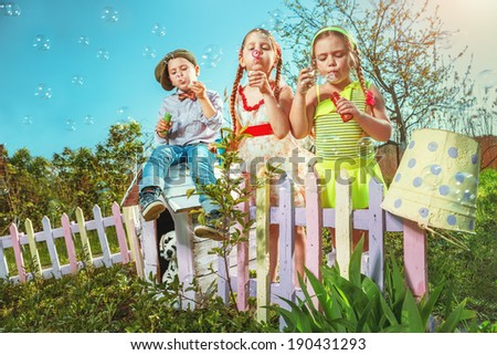Cute little girls with boy are blowing a soap bubble - stock photo