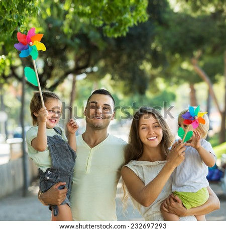Cute little girls with windmills sitting on parent's arms outdoor  - stock photo