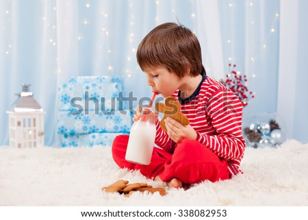 Cute little happy boy, eating cookies and drinking milk, waiting for Santa in pajama on Christmas Eve night - stock photo