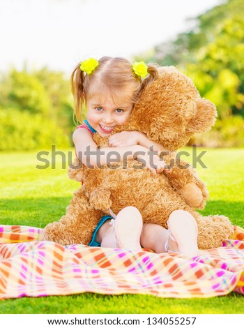 Cute little happy girl hugging big brown teddy bear and sitting down on green grass meadow, spring season - stock photo