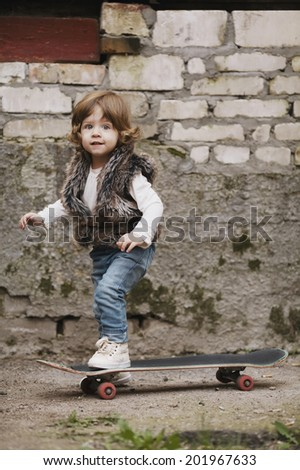 cute little hipster girl with skateboard portrait - stock photo