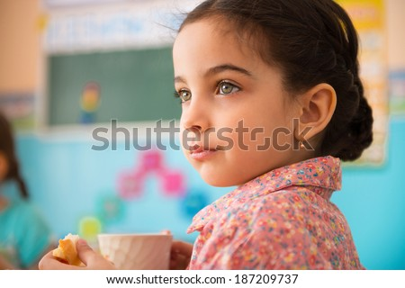 Cute little hispanic girl with cup of milk at daycare - stock photo
