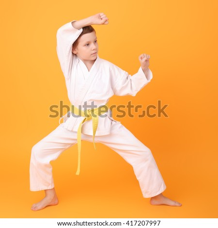 cute little karate boy on the yellow background - stock photo