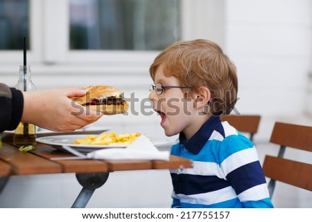 Cute little kid boy eating fast food: french fries and hamburger in cafe - stock photo