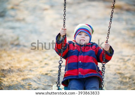 Cute little kid boy having fun with chain swing on outdoor playground. child swinging on warm sunny spring or autumn day. Active leisure with kids. Boy wearing colorful clothes - stock photo