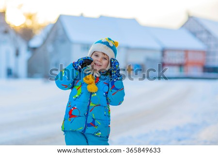 Cute little kid boy in colorful winter clothes having fun, outdoors during snowfall. Active outdoors leisure with children in winter. Happy child with warm hat, h gloves, winter fashion - stock photo