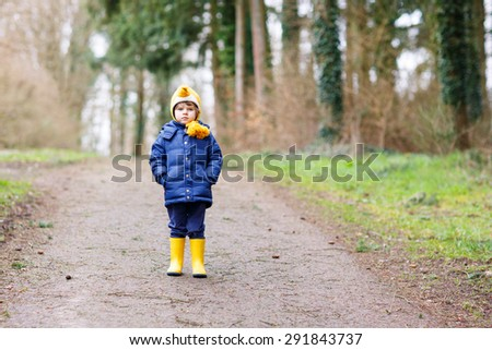 Cute little kid boy walking through autumn forest. Child in yellow waterproof rainboots. Active leisure with kids outdoors. - stock photo