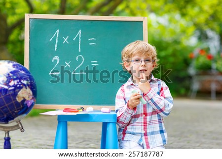 Cute little kid boy with glasses at blackboard practicing mathematics, outdoor. school or nursery. Back to school concept - stock photo