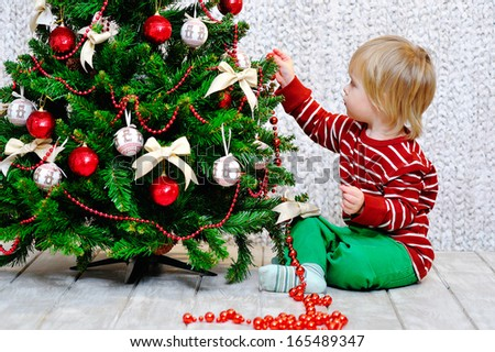 Cute little kid sitting down on the wooden floor and decorating Christmas tree with red garland - stock photo