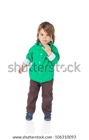 Cute little kid, 2 years old boy, standing and looking at camera, wearing shirt and jeans. High resolution image isolated on white background with copy space. Studio shot. - stock photo