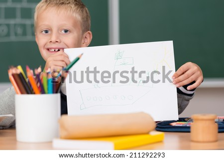 Cute little kindergarten schoolboy holding up a blank sheet of white paper in front of a container filled with colored pencil crayons in a concept of art and creativity - stock photo