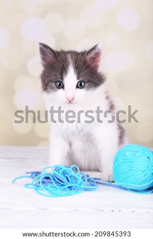 Cute little kitten playing with thread ball on light background - stock photo