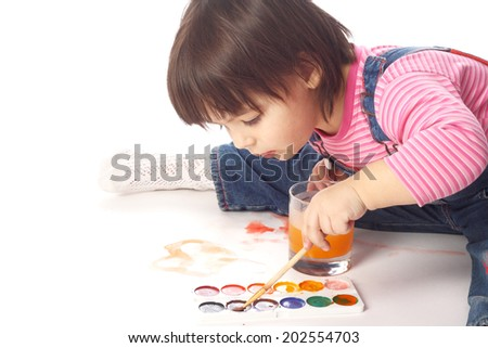 cute little left handed child painting with watercolors in studio - stock photo