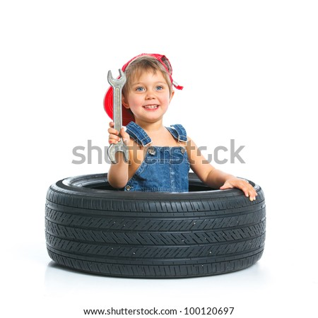 Cute little mechanic with a tire and wrench - stock photo