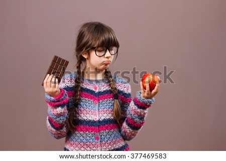 Cute little nerdy girl would rather eat candy than fruit.I would rather eat chocolate ! - stock photo